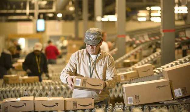 An Amazon.com employee grabs boxes off the conveyor belt to load in a truck at their Fernley, Nev., warehouse on Monday, Dec., 1, 2008.  Amazon.com spokeswoman Sally Fouts said the company couldn't comment on sales traffic or predict how much business would come at the last minute for holiday online shopping. (AP Photo/Scott Sady)